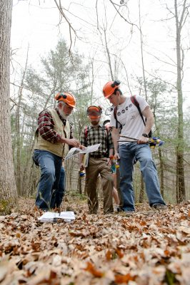 students and instructor working in forest with a map